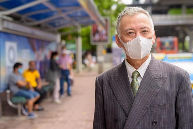 Dojrzały japoński biznesmen z maskową pozycją z odległością przy przystankiem autobusowym