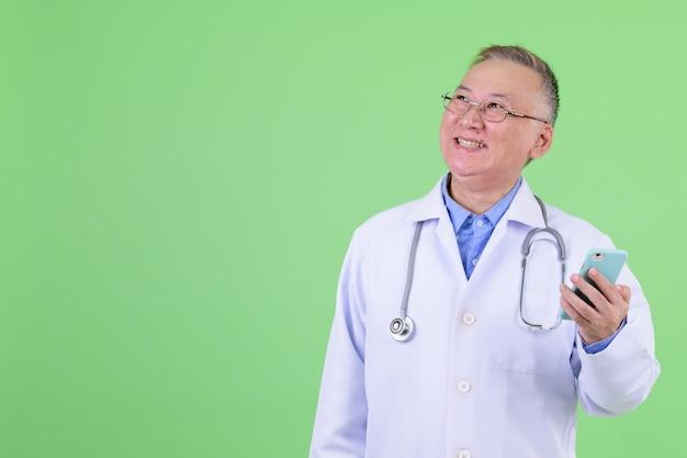 Dojrzały japoński lekarz mężczyzna z okularami przed kluczem chrominancji z zieloną ścianą