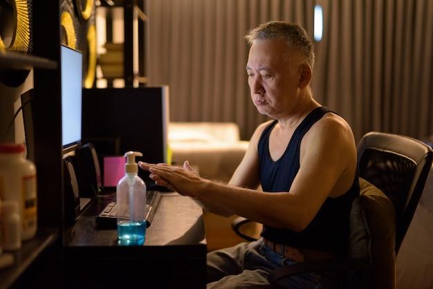 Dojrzały japoński mężczyzna używa dezynfekatora ręki podczas gdy pracujący od domu