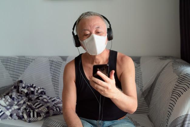 Dojrzały japoński mężczyzna z maską słucha muzyki podczas gdy używać telefon w domu pod kwarantanną