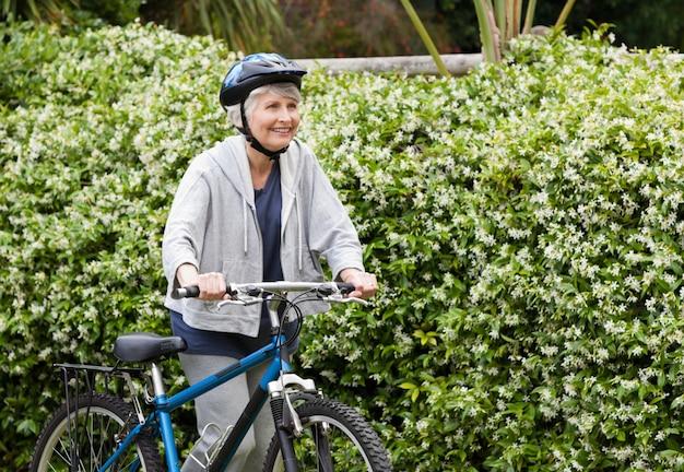 Dojrzały kobiety odprowadzenie z jej rowerem górskim