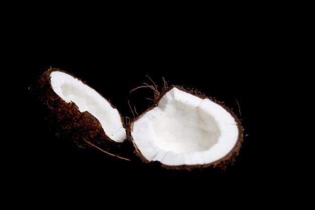 Dojrzały kokos jest podzielony na dwie połówki odizolowane na czarno