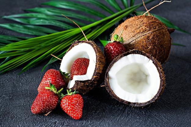Dojrzały kokos z liśćmi palmowymi i dojrzałymi świeżymi truskawkami w pół kokosa na ciemnym tle. letnie owoce, zdrowe odżywianie i pyszny surowy deser. koncepcja zdrowej żywności, wegańskie jedzenie.