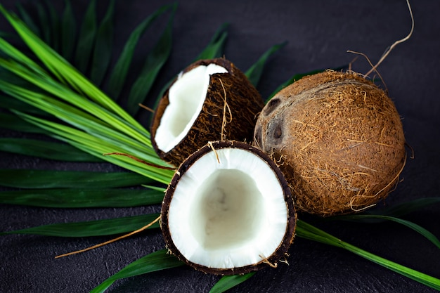 Dojrzały kokos z palmą opuszcza na ciemnym tle. letnie owoce, zdrowe jedzenie koncepcja. zdrowa koncepcja i spa