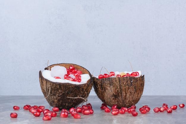 Dojrzały kokos z pestkami granatu umieszczonymi na marmurowej powierzchni