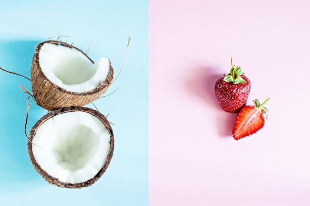 Dojrzały kokos ze świeżymi truskawkami na różowo-niebieskim tle. letnie owoce, zdrowe jedzenie koncepcja. przydatny dla ciała, zdrowej koncepcji i koncepcji spa.