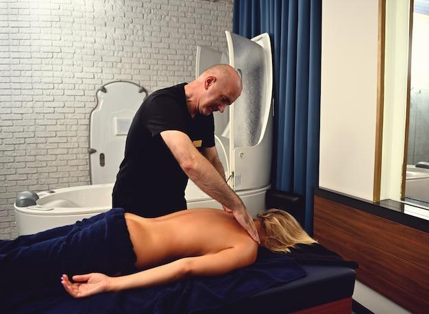 Dojrzały kręgarz masujący młodego pacjenta centrum odnowy biologicznej. masaż ajurwedyjski w nowoczesnym salonie spa.