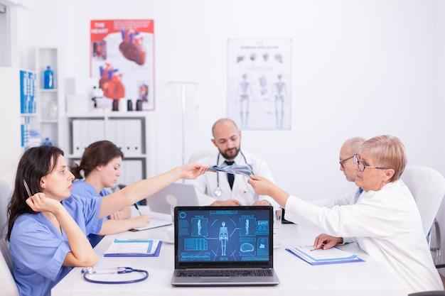 Dojrzały lekarz dający radiografii młodej pielęgniarce podczas spotkania personelu w sali konferencyjnej. ekspert kliniczny terapeuta rozmawiający z kolegami o chorobie, specjalista od medycyny.
