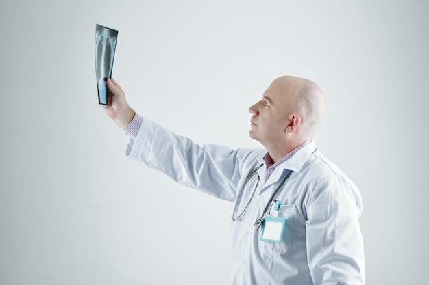 Dojrzały lekarz w białym fartuchu badający zdjęcie rentgenowskie w dłoni stojącej na białym tle
