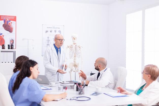 Dojrzały lekarz w okularach trzymając prezentację o anatomii człowieka za pomocą szkieletu. ekspert kliniczny terapeuta rozmawiający z kolegami o chorobie, specjalista od medycyny