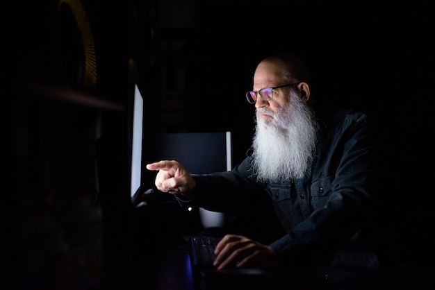 Dojrzały łysy brodaty mężczyzna pracuje po godzinach w domu w ciemności