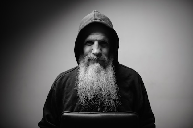 Dojrzały łysy mężczyzna z długą siwą brodą na białej ścianie w czerni i bieli