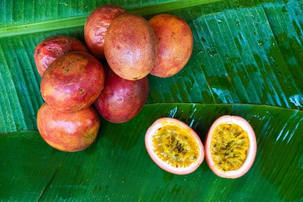 Dojrzały marakuja na mokrym liściu bananowca. witaminy, owoce, zdrowa żywność