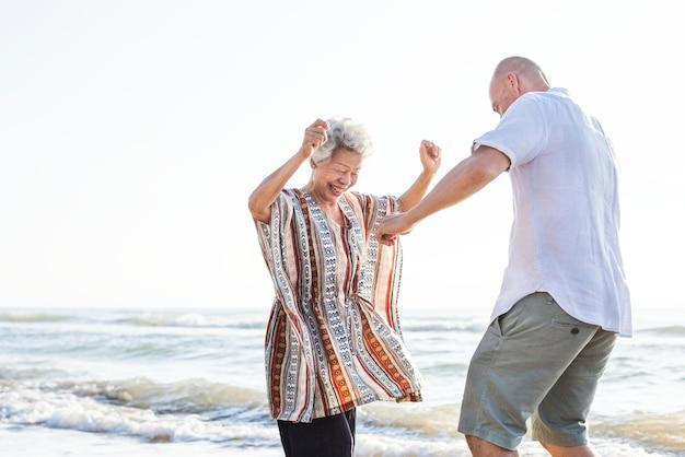 Dojrzały matki i syna taniec na plaży