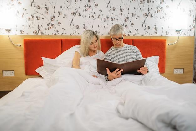 Dojrzały mąż i żona patrzy na album ze zdjęciami w sypialni. mężczyzna i kobieta leżąc w łóżku przed snem, szczęśliwa para miłości
