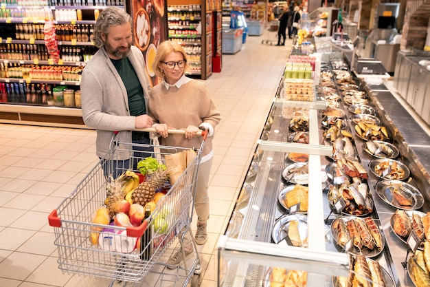 Dojrzały mąż i żona pchają wózek na zakupy ze świeżymi produktami spożywczymi, poruszając się wzdłuż dużego wyświetlacza z owocami morza w supermarkecie