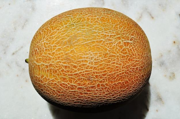 Dojrzały melon. żółty melon na jasnym tle. tło, tekstura, tapeta.