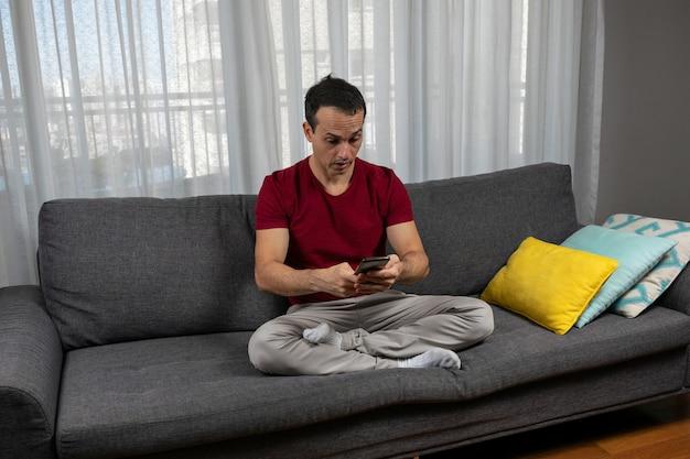 Dojrzały mężczyzna (44 lata) siedzący ze skrzyżowanymi nogami na sofie i bardzo zaskoczony widokiem swojego smartfona.