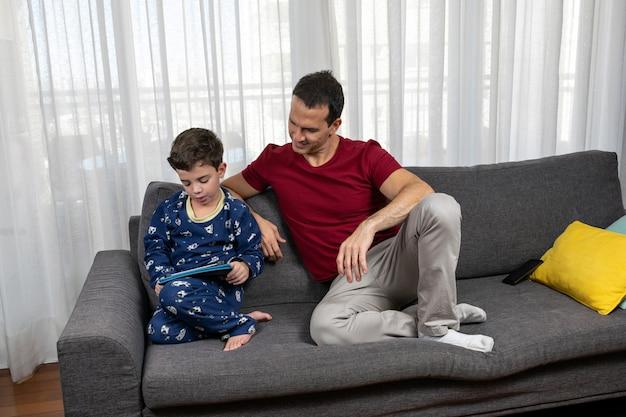 Dojrzały mężczyzna (44 lata) siedzi obok syna (7 lat) i uśmiecha się do niego.