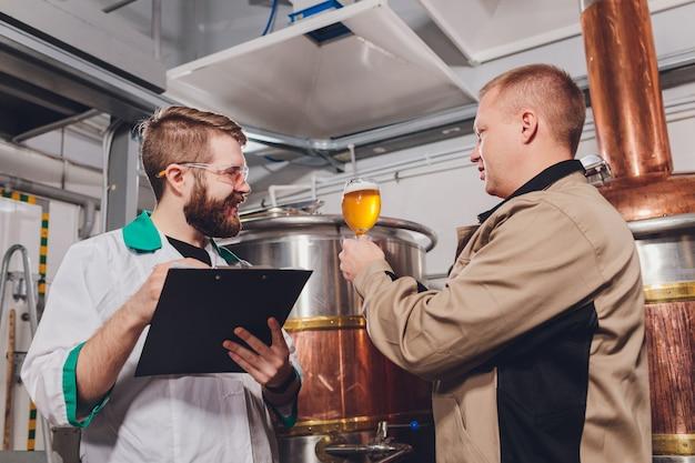 Dojrzały mężczyzna bada jakość piwa rzemieślniczego w browarze. inspektor pracujący w fabryce produkcji alkoholu sprawdzający piwo. człowiek w gorzelni kontroli kontroli jakości piwa z beczki.