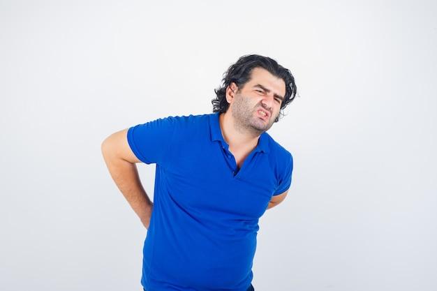 Dojrzały mężczyzna cierpiący na bóle pleców w niebieskiej koszulce i wygląda na zmęczonego. przedni widok.