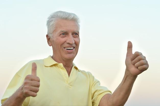 Dojrzały mężczyzna cieszący się świeżym powietrzem na łonie natury z kciukami do góry