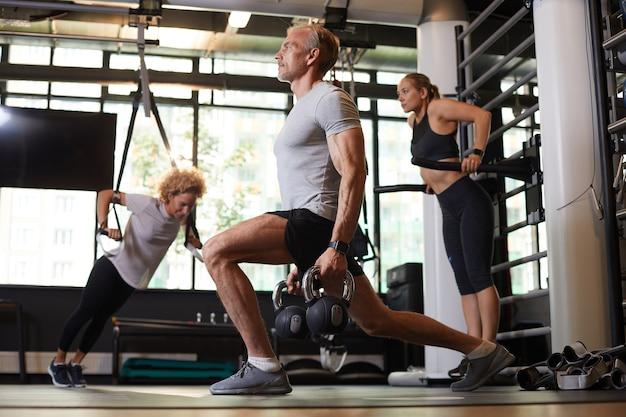 Dojrzały mężczyzna ćwiczy z hantlami w ym z dwiema kobietami w tle
