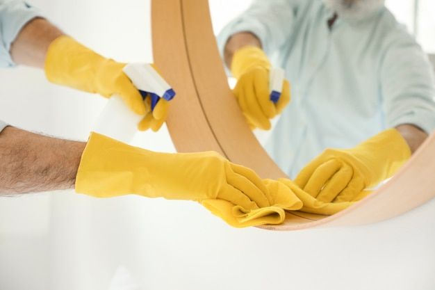 Dojrzały mężczyzna do czyszczenia lustra w domu, zbliżenie