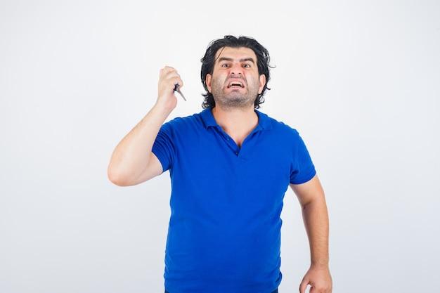 Dojrzały mężczyzna grozi nożyczkami w niebieskiej koszulce i wygląda agresywnie, z przodu.