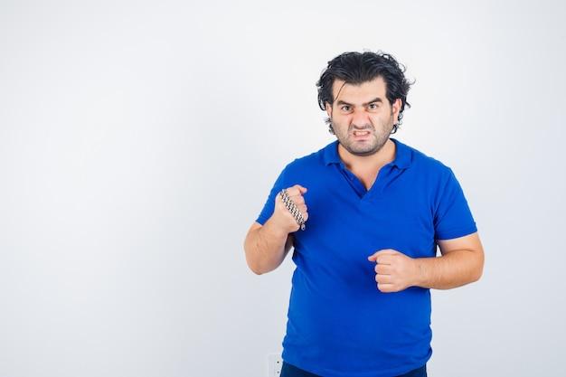 Dojrzały mężczyzna grozi z łańcuchem owiniętym w pięść, zaciskając zęby w niebieskiej koszulce i wyglądając agresywnie. przedni widok.