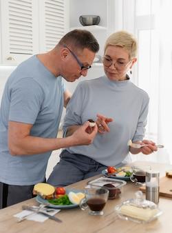 Dojrzały mężczyzna i kobieta je zdrowe jedzenie ze świeżymi warzywami na kuchni szczęśliwego życia na emeryturze
