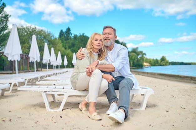 Dojrzały mężczyzna i kobieta odpoczywają na brzegu morza