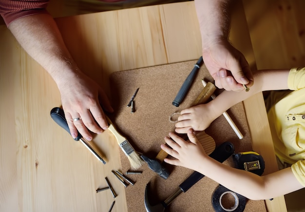 Dojrzały mężczyzna i mały chłopiec razem tworzą drewnianą zabawkę.