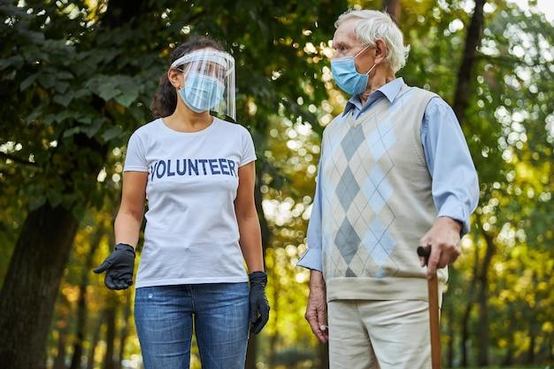 Dojrzały mężczyzna i piękna kobieta w maskach ochronnych podczas rozmowy na placu miejskim
