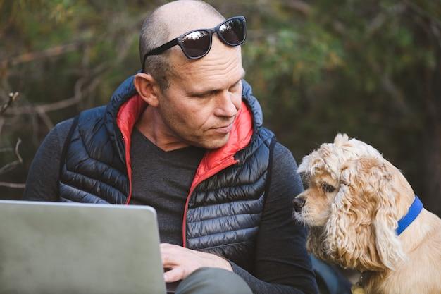 Dojrzały mężczyzna i słodki pies z laptopem