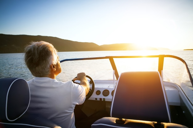 Dojrzały mężczyzna jeżdżący łodzią motorową o zachodzie słońca