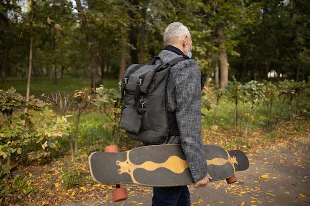 Dojrzały mężczyzna jeździ na deskorolce w parku podczas pandemii