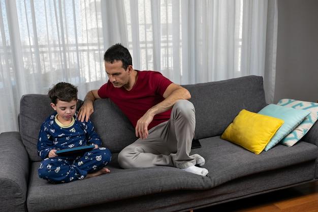 Dojrzały mężczyzna lat siedzi obok swojego syna lat z ręką na jego ramieniu.