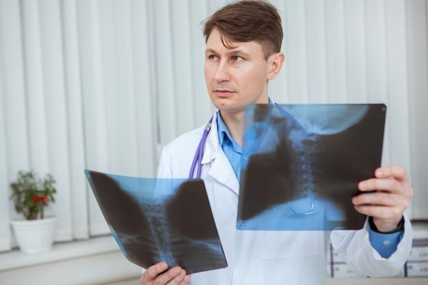 Dojrzały mężczyzna lekarz odwracając wzrok w zamyśleniu, badając prześwietlenie szyi pacjenta