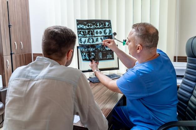 Dojrzały mężczyzna lekarz patrząc na zdjęcie rentgenowskie i pokazując szczegóły pacjentowi w nowoczesnym biurze. koncepcja opieki zdrowotnej, rentgen, ludzie i medycyna.