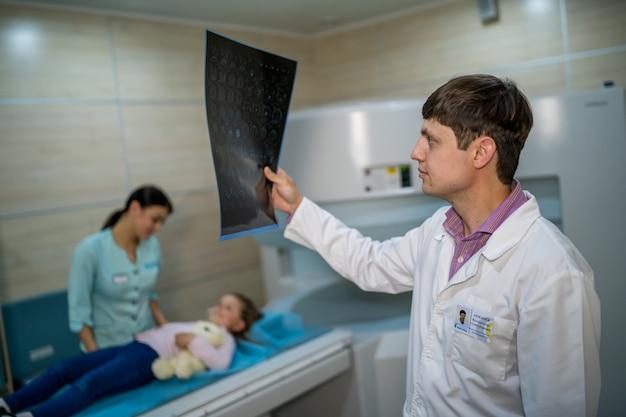 Dojrzały mężczyzna lekarz patrząc na zdjęcie rentgenowskie na białym tle na tle nowoczesnego biura. koncepcja opieki zdrowotnej, rentgen, ludzie i medycyna.