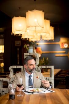 Dojrzały mężczyzna pije czerwone wino podczas lunchu