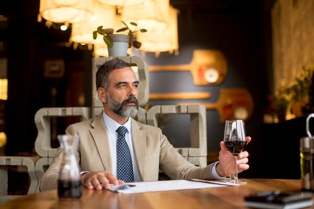 Dojrzały mężczyzna pije kieliszek czerwonego wina w restauracji
