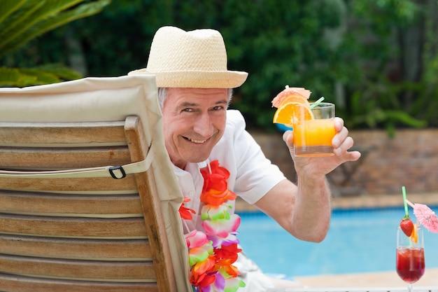 Dojrzały mężczyzna pije koktajl obok pływackiego basenu