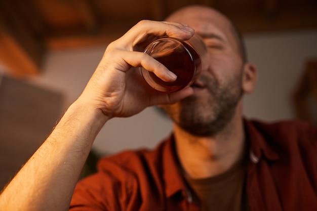 Dojrzały mężczyzna pije mocny alkohol ze szkła w domu
