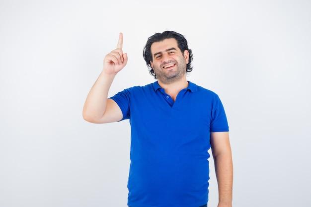 Dojrzały mężczyzna podnosi palec wskazujący w niebieskiej koszulce