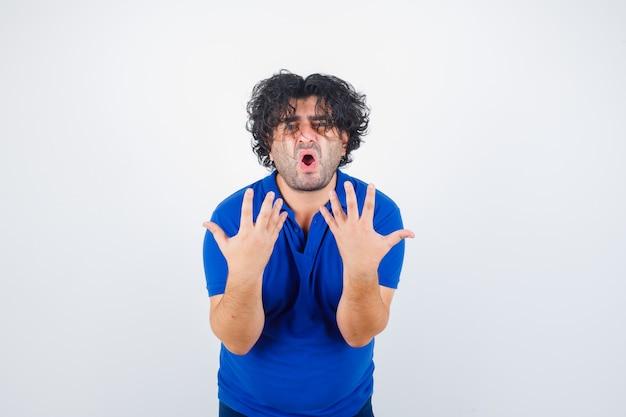 Dojrzały mężczyzna podnosi ręce w agresywny sposób w niebieskiej koszulce i patrzy tęsknie. przedni widok.