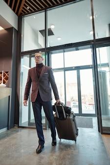 Dojrzały mężczyzna podróżujący w interesach ciągnie walizkę wchodząc do hotelowego salonu po przyjeździe do obcego kraju
