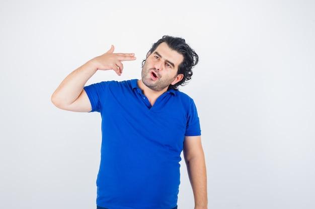 Dojrzały mężczyzna pokazuje gest samobójstwa w niebieskiej koszulce i wygląda zamyślony. przedni widok.
