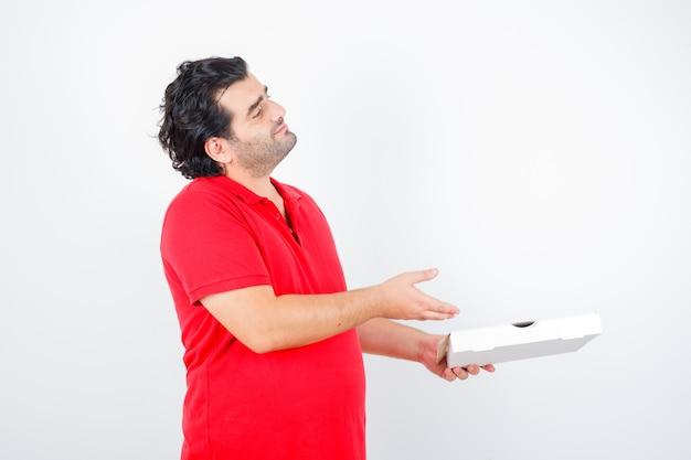 Dojrzały mężczyzna pokazuje pudełko po pizzy w czerwonej koszulce i wygląda pewnie, widok z przodu.
